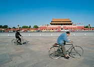China, Beijing, two people riding bicycles in street in front of The Forbidden City