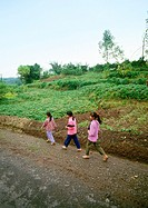 China, Guangxi Autonomous Region, children walking along dirt road in rural area