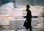 Israel, Jerusalem, Orthodox Jew walking by barrier, side view, blurred