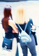 Two women folding arms, rear view, blurred