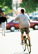 Person riding bike in street, rear view