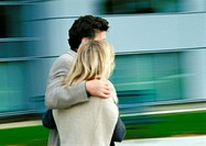 Man and woman walking together, man's arm around woman, blurred