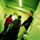 Young man standing in subway corridor, side view, people walking, rear view in background