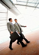 Businessmen walking together with briefcases, indoors