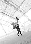 Businessman waving hand and briefcase, blurred b&amp;w