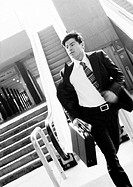 Businessman hurrying away from escalator, holding briefcase, blurred motion, b&amp;w
