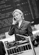 Businesswoman on cell phone with luggage caddy, in front of arrival and departure board, b&w