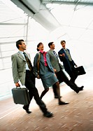 Group of business people walking together indoors, blurred