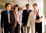 Group of business people walking together indoors, front view