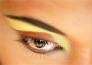 Woman´s eye with yellow and orange eye shadow, extreme close-up, blurred
