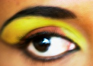Woman´s eye with yellow and orange eye shadow, extreme close-up