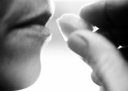 Close up of hand bringing food to woman´s mouth, black and white, side view
