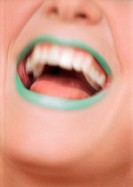 Close up of woman´s mouth open and smiling with green lipstick, blurred