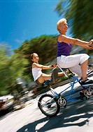 Mature woman and girl riding bikes, blurred