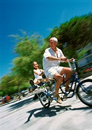 Mature man and girl riding bikes, blurred motion