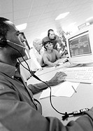 Man with headset using computer, colleagues in blurred background, B&W