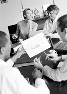 Businesspeople in conference examining document, blurred foreground, B&W