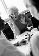 Mature businesswoman using cell phone, colleagues in blurred foreground, B&W