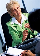 Businesswoman listening to colleague, blurred foreground