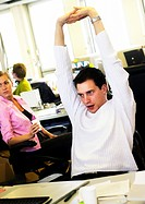 Man stretching in office, colleagues in background
