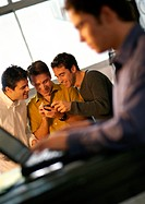 Three men looking at hand held computer, fourth man using laptop in foreground
