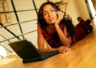 Woman lying on floor with laptop computer