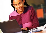 Woman with laptop computer, smiling, portrait