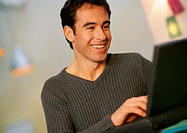 Man using laptop computer, smiling, close-up