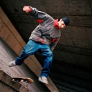 Young man in mid-air jump with skateboard
