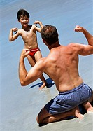 Man and child facing each other, flexing on beach
