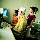 Mature man and two girls using computer