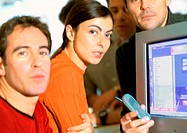 Adults grouped around computer screen, close-up, looking at camera