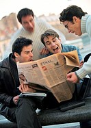 Four men looking at newspaper