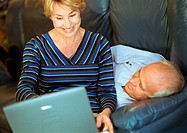 Mature couple, woman using laptop, man lying down