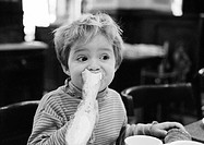 Young child eating bread, portrait, b&w