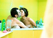 Couple sitting in bathtub, kissing, side view