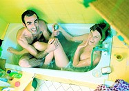 Couple playing in bathtub, high angle view