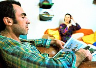 Man reading magazine, woman sitting in background