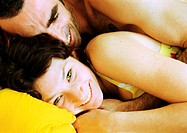 Couple in bed, man lying on woman's back, close-up