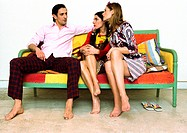 Man sitting on sofa with legs apart looking at two women sitting next to him with legs crossed