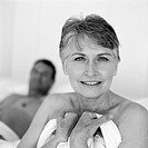 Mature woman holding sheet against chest, man lying behind her, portrait, b&w