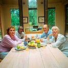 Four mature people sitting at table, sticking out tongues