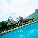 Mature couple lying in lounge chairs beside swimming pool