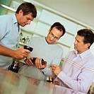 Three men looking at wine bottle