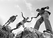 Three young people climbing on rocks, woman being aided, low angle view, b&w