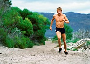 Man in shorts running along Mountain trail