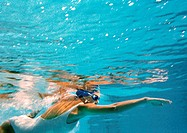Woman swimming underwater, underwater view