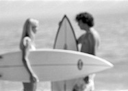 Couple holding surfboards, talking, blurred, b&w