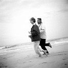 Mature couple running on beach, b&w