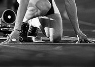 Male runner at starting block, low angle view, close-up, b&w